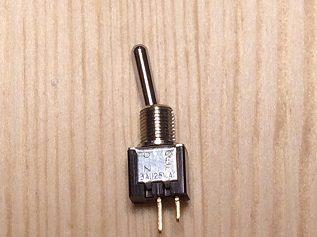7. 今回使ったトグルスイッチです。 3Aの「単極単投」というタイプで、ハンダ付けする接点が2本の一番単純なタイプです。  ネジの上の頭部分から下の接点の先までが、板の厚み18ミリの中に納まる必要があるので、かなり小さめのスイッチになりました。