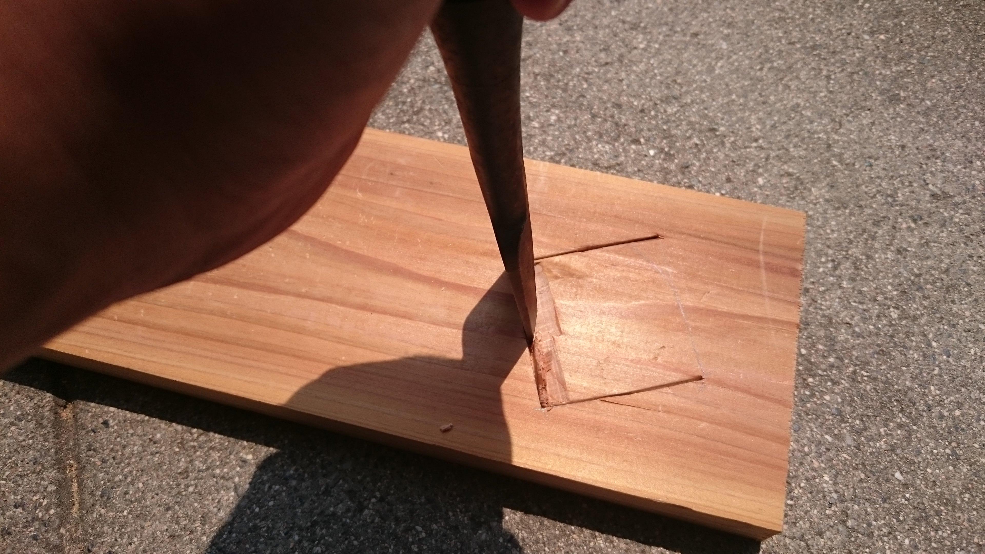 1. ノミで杉板に45mmの正方形の穴をあけます。 いきなり墨のラインで彫っちゃってますが、本当は最初に墨の少し内側で彫ってから仕上げに墨のラインで削ると綺麗にあけれます。