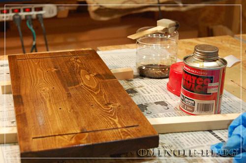 STEP.4 用意したセリアのブックエンドがベージュ色なので、ベースはワトコのダークウォルナットで濃いめに塗装。 オイル系の塗装で役に立つのは写真奥に見えるオリジナルのスポンジブラシ。 薄い板に、3cm幅の隙間テープ(スポンジ状の、扉の隙間をふさぐ為に取り付けるテープ)を短く切ったものを折り曲げてブラシ状にしたものです。 使い捨て出来るし、かなり経済的です。スポンジなので塗りむらや毛が抜けることもなく、便利!