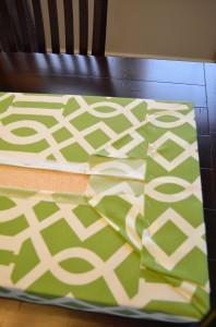 2. 作業台の上に布、フォーム、ボードを順番に置きます。そして布を真っすぐ、しっかりと引っ張りホッチキスで留めます。
