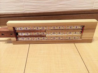 13. アルミパイプを立てて配線を通した後で200ミリにカットした3本のLEDテープライトを溝の中に貼り、配線をハンダ付けしてつなぎます。  テープライトは50ミリピッチでハサミで簡単にカット出来ます。  LEDの素子がテープ50ミリあたり3個ついていて、今回は36個素子があります。 光の量は計算上720ルーメンとなり、かなり明るいデスクライトです。  この画像の真ん中のラインが左のアルミパイプ内の配線につながっていて、真ん中→上→下のテープライトの順に右と左の溝でつなげて配線しています。 下のテープライトの最後の右端は切りっぱなしです。  左右に見えている配線はこの後、薄い杉材で隠しています。